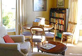 The Living Room/Study is warmly furnished with comfortable chairs, an antique dining table, Persian rug and books and magazines - perfect for reflecting, reading and conversation.